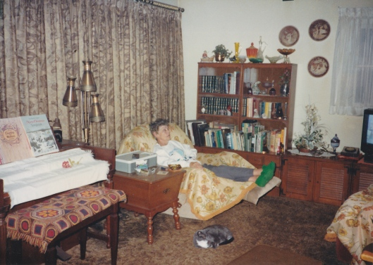 Aunt Georgia in her living room.  The rug covering the bench of her organ was originally my Grandma Taylor's and it is in my care for the time being.  Her cat, Felicia, is laying on the floor near her.